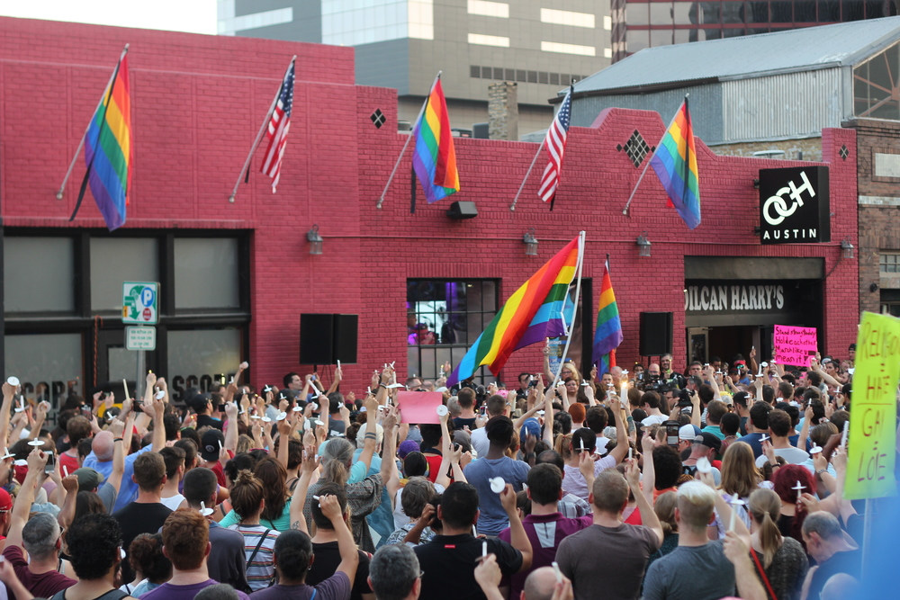 """The crowd holds up their burned-out candles, chanting, """"We're queer, we're here, get used to it!"""""""