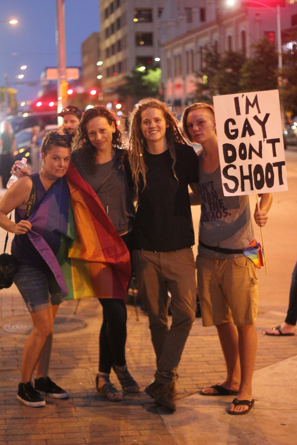 """Lisa Hause, Katie Trundt, Lacey Roop and Caitlyn Krull had a poster party before the vigil. Caitlyn's poster reads, """"I'm gay don't shoot."""""""