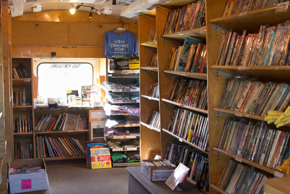 The inside of a converted mini bus, that now serves as Fifth Dimension books.