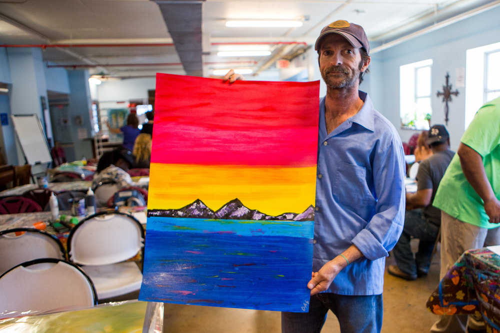 Schumaker showcases his landscape painting of mountains, the ocean and a sunset.