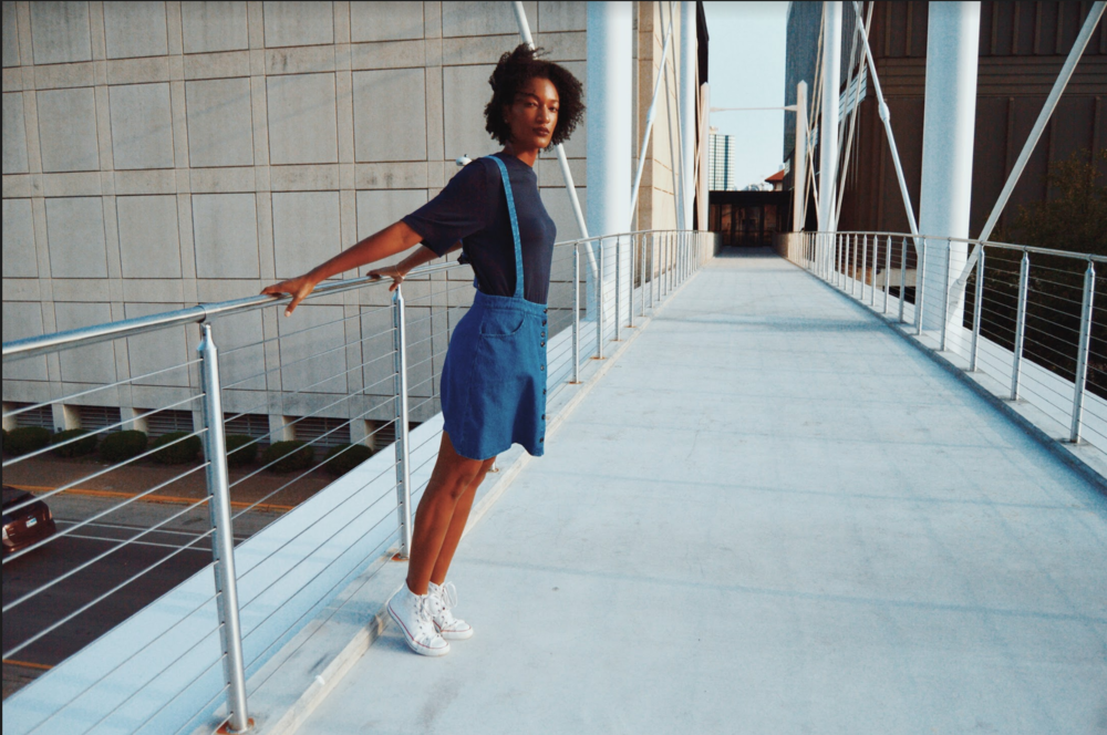 Griffith rocks a pair of dark blue denim overalls by Loup and a navy blue T-shirt by The Fifth Label. Shoes pictured are model's own.