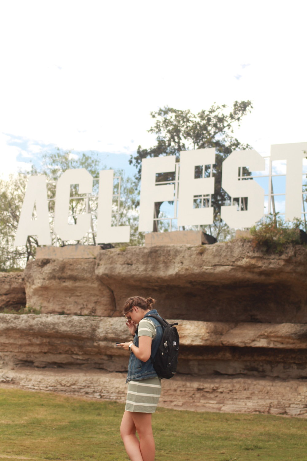 Many pose in front of the ACL Fest sign.
