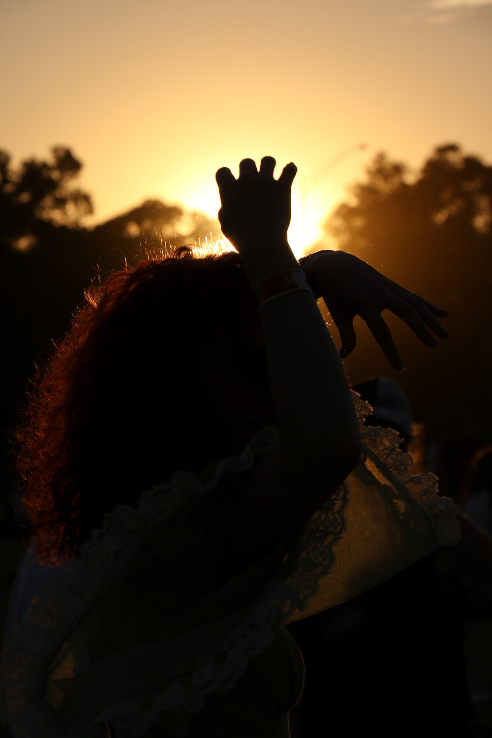 A woman dances in the sunset to one of the night's shows.