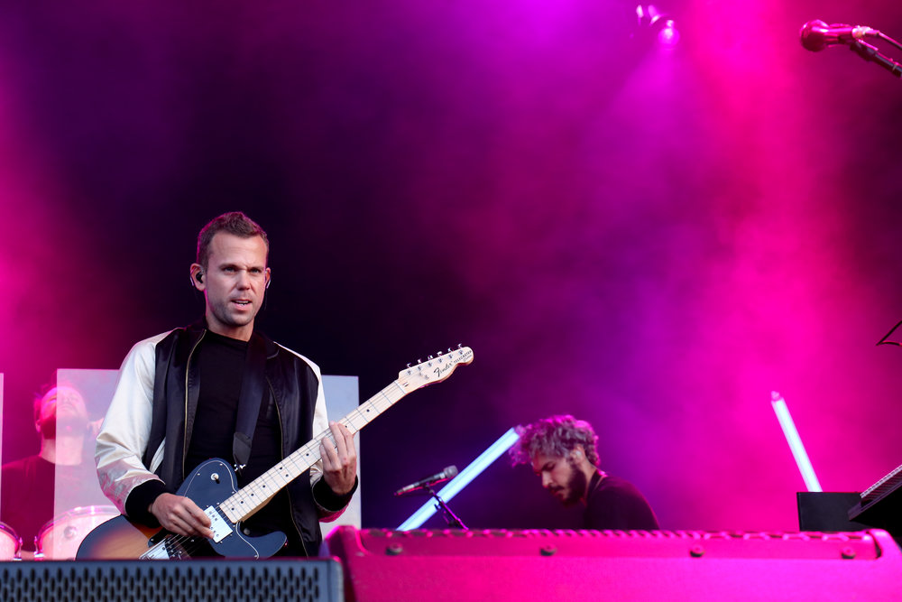 Frontman of M83 stares into the field of fans.