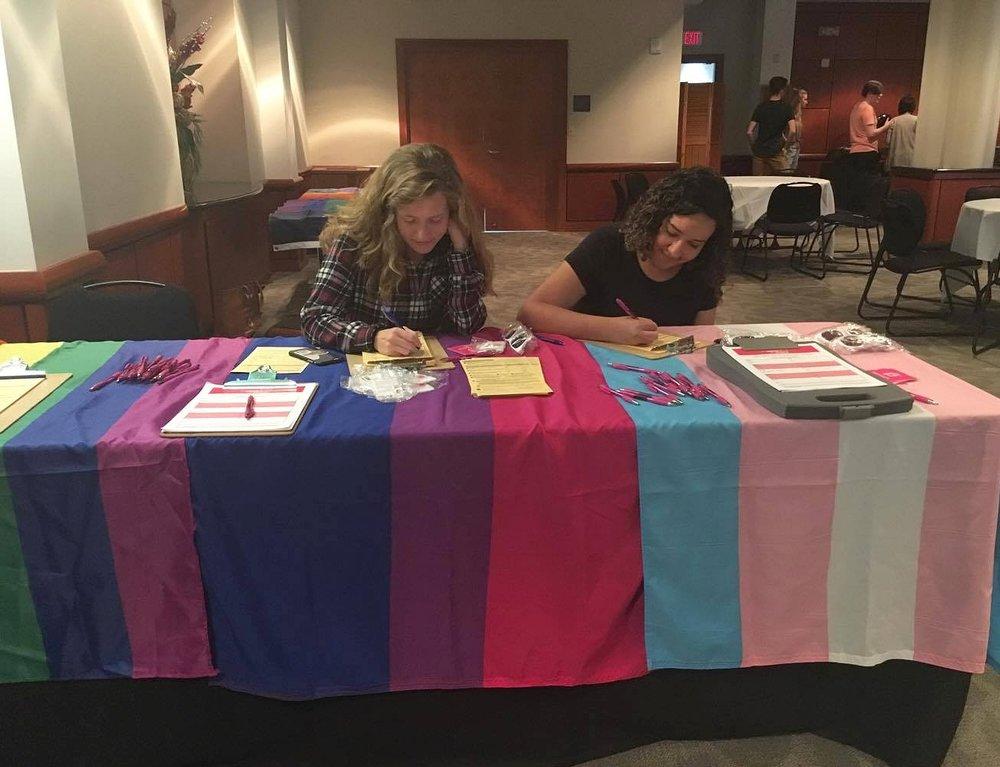 Volunteer deputy registrars help students register to vote.