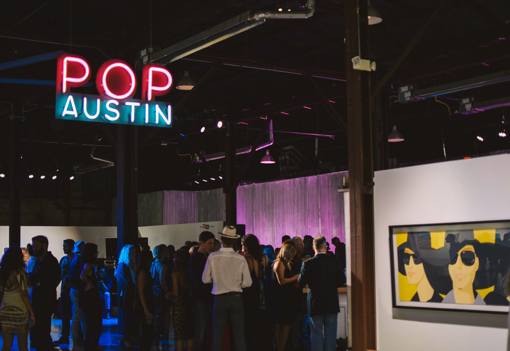 Attendees enjoy drinks as they observe the art at POP Austin.