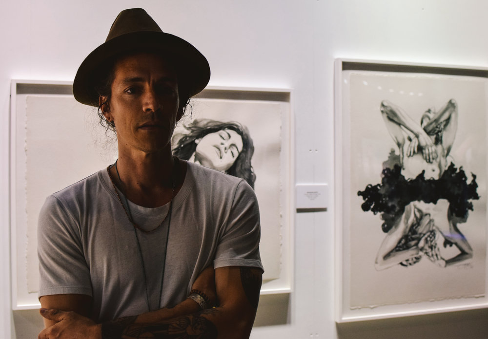 Brandon Boyd of Incubus poses in front of his artwork.