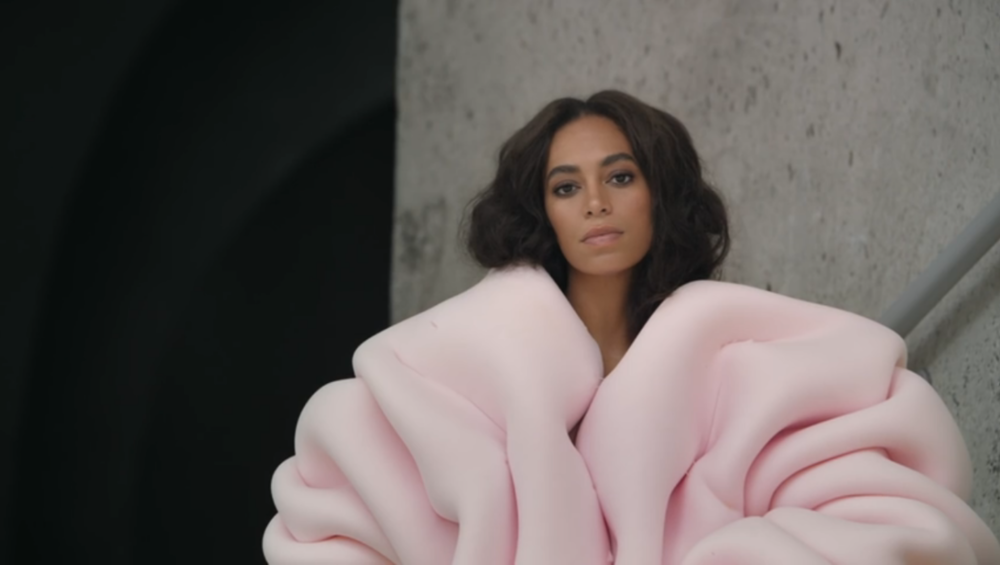 Solange donning an oversized pastel pink coat.