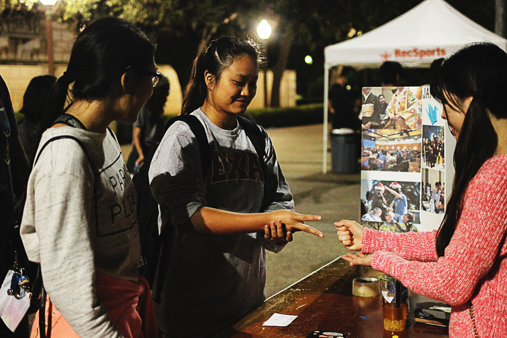 At one game booth, students play a game of rock-paper-scissors.