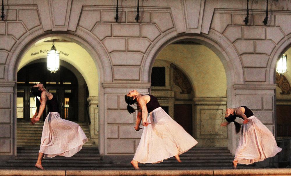 Dancers synchronize a fall.