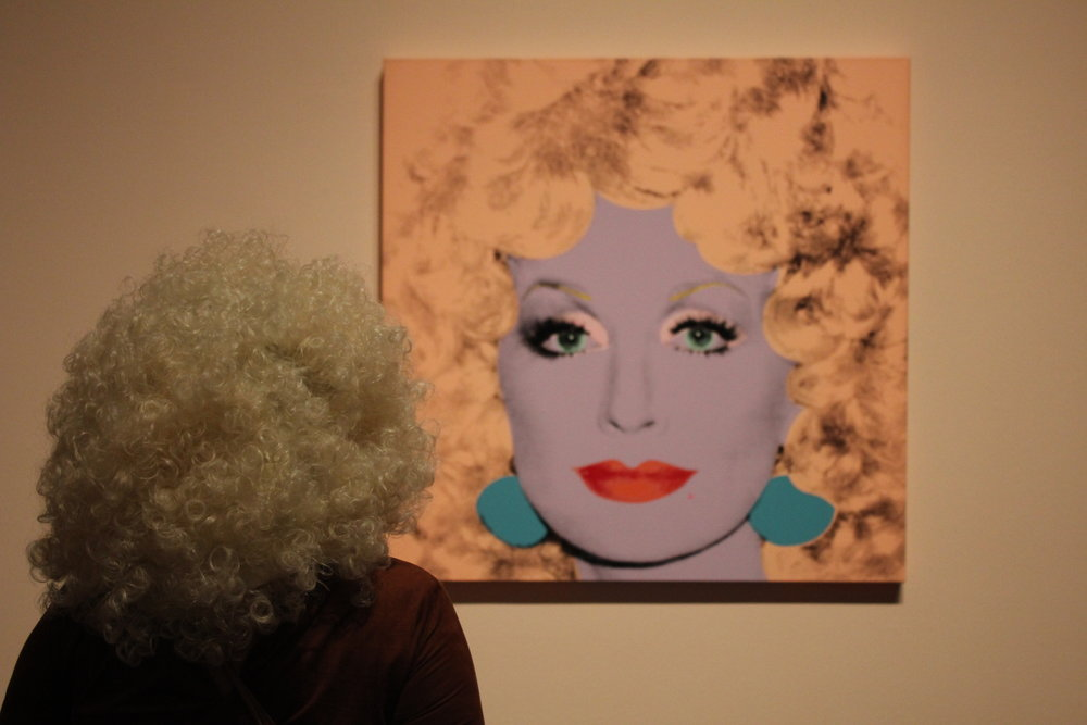 An attendee dressed as Dolly Parton admires the pop-country icon's portrait.