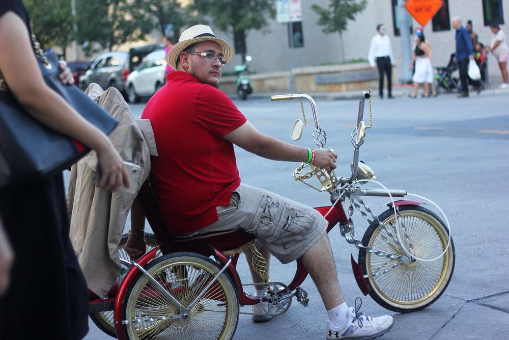 Man rides his low-rider bicycle from one end of the festival grounds to the other.