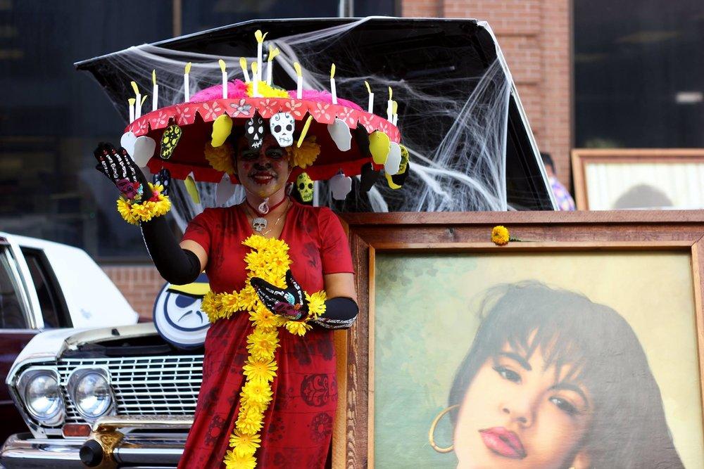 A woman dressed as La Calavera Catrina poses next to a painting of Selena Quintanilla.