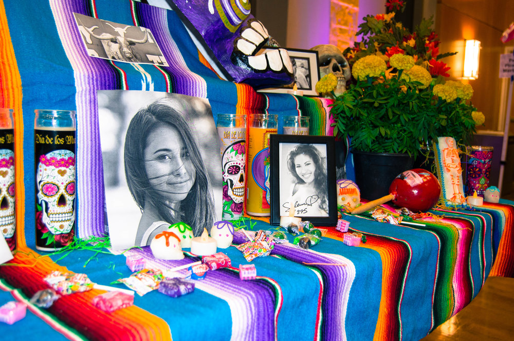 A photo of Haruka Weiser was surrounded by candles, Mexican candy and marigolds at MACC's community altar.