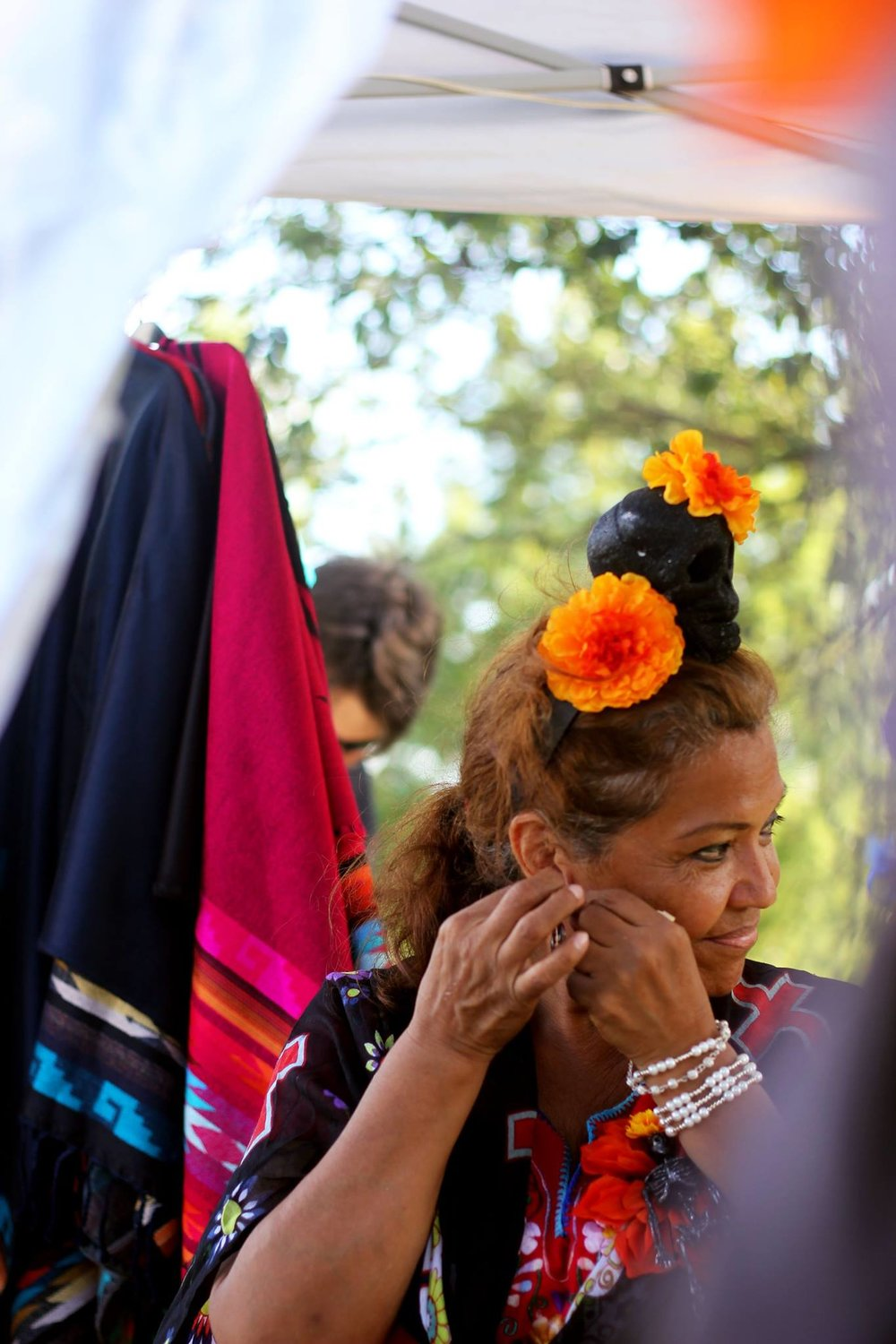 Many vendors made their way to the music festival bringing with them a variety of Mexican knick knacks like bags with the colors of the Mexican flag, traditional embroidered blouses, and jewelry. A vendor looks around while putting on her earrings.