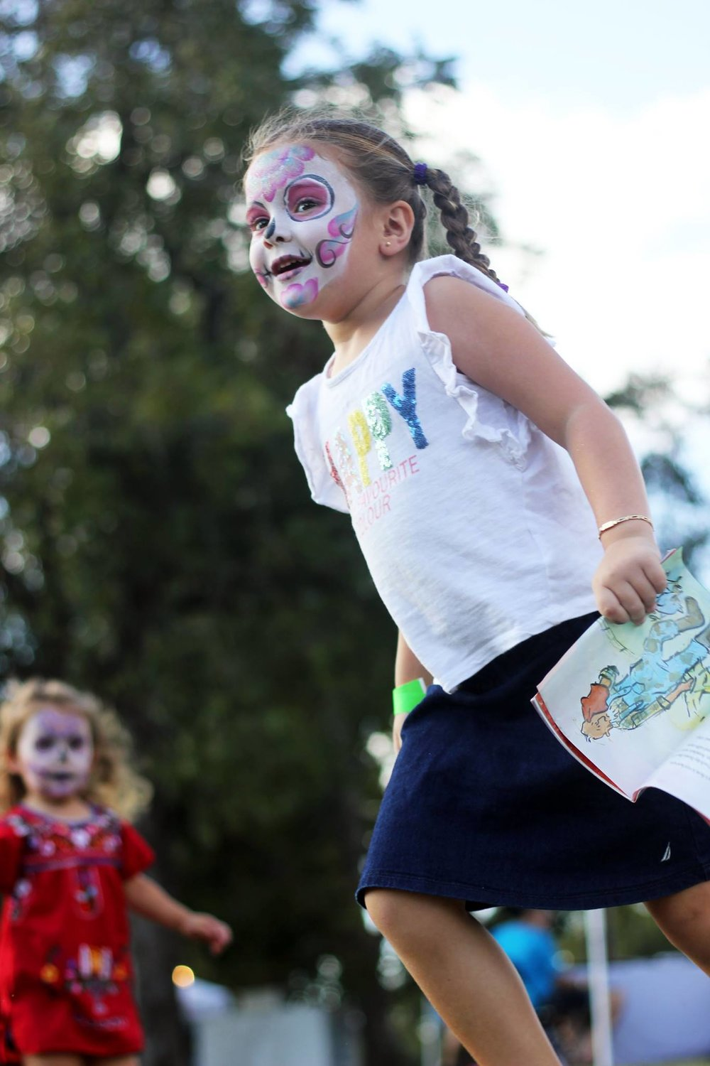 Two children run around after getting their faces painted.