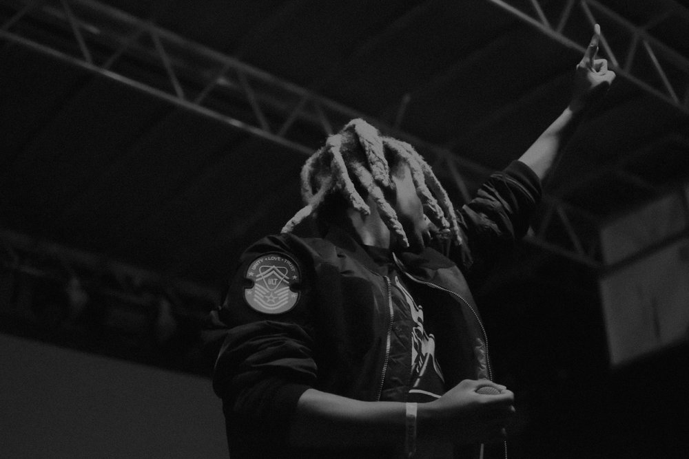 Denzel Curry wears a bomber jacket while performing on stage.