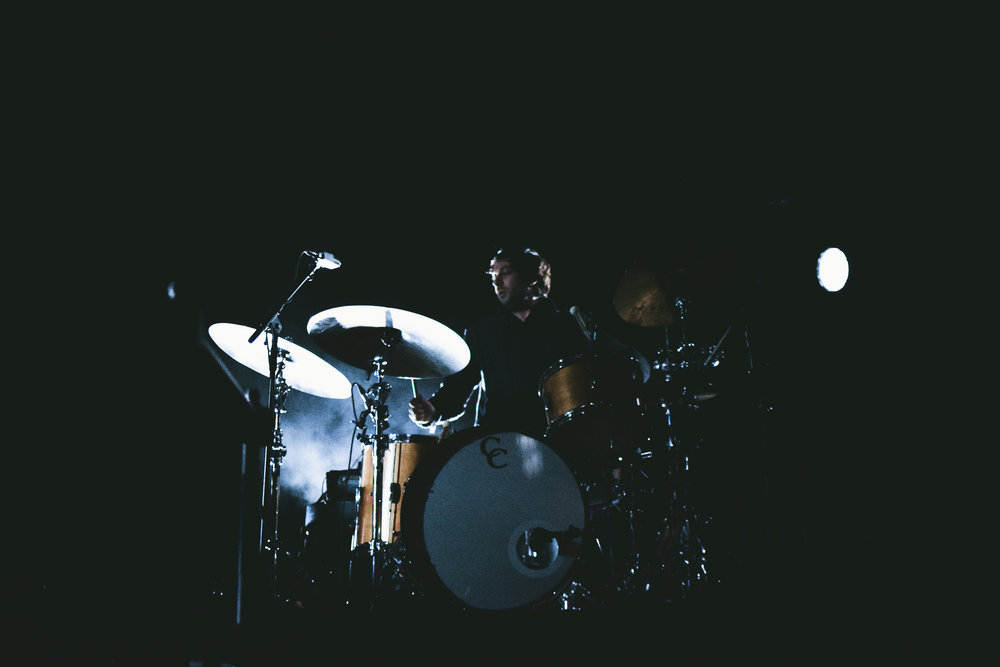 Drummer of Beach House sets up his drum set for the performance.