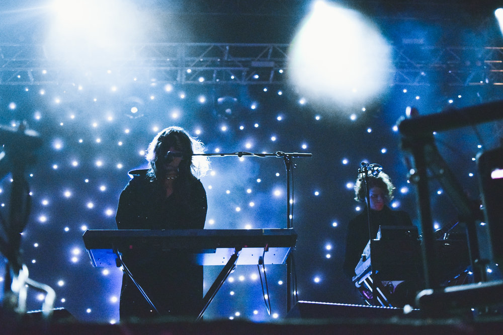 Victoria Legrand of Beach House looks mysterious in her dark cloak and starry background.
