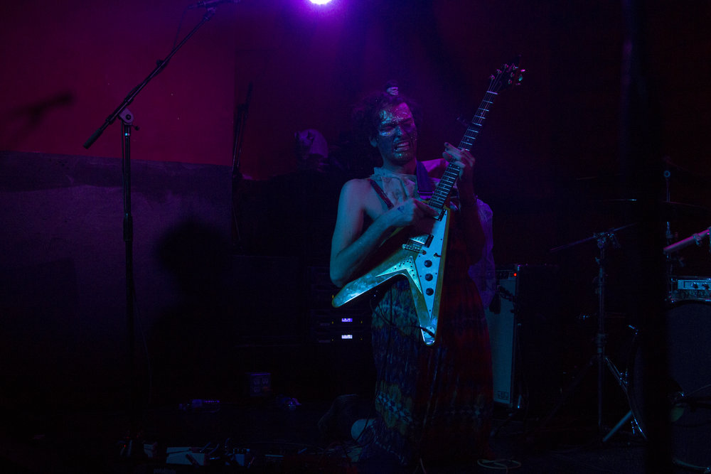 Lead guitarist Ben Hopkins performs with a face full of glitter and stickers.