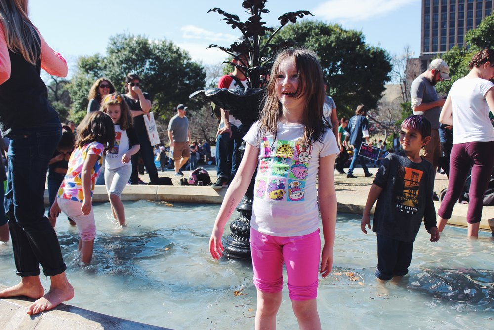 Children splash in the Capitol pond during the speeches.