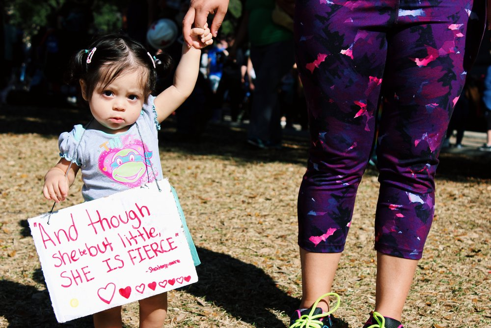 "A young girl holds a sign that says, ""'And though she be but little, she is fierce' -Shakespeare."" Many young children joined their parents and families at the Women's March."
