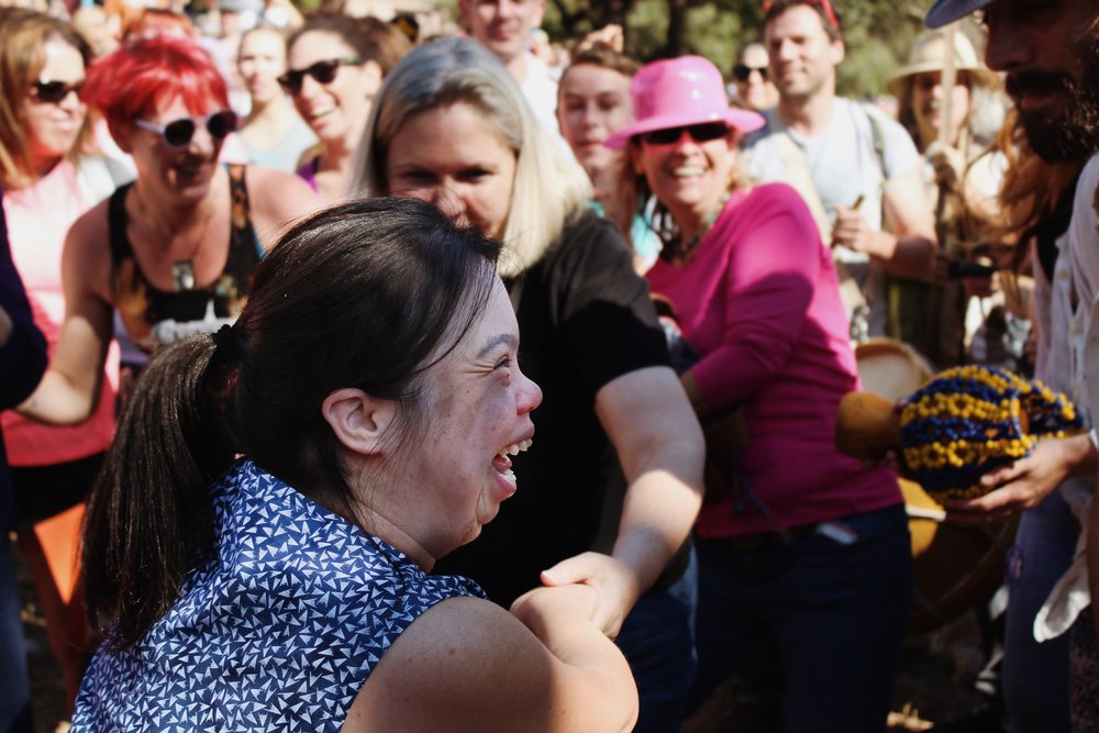 A woman joins people of all ages dancing to the upbeat music of drums.