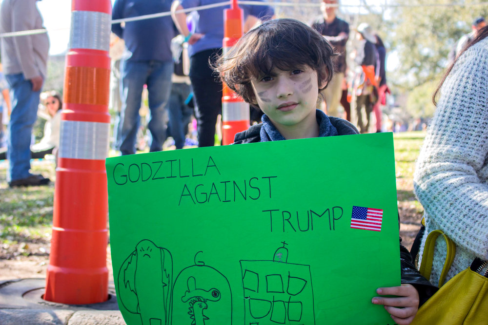 "Leo Acton holds a green sign that says, ""Godzilla against Trump"" at the ""No Ban, No Wall rally on Saturday."