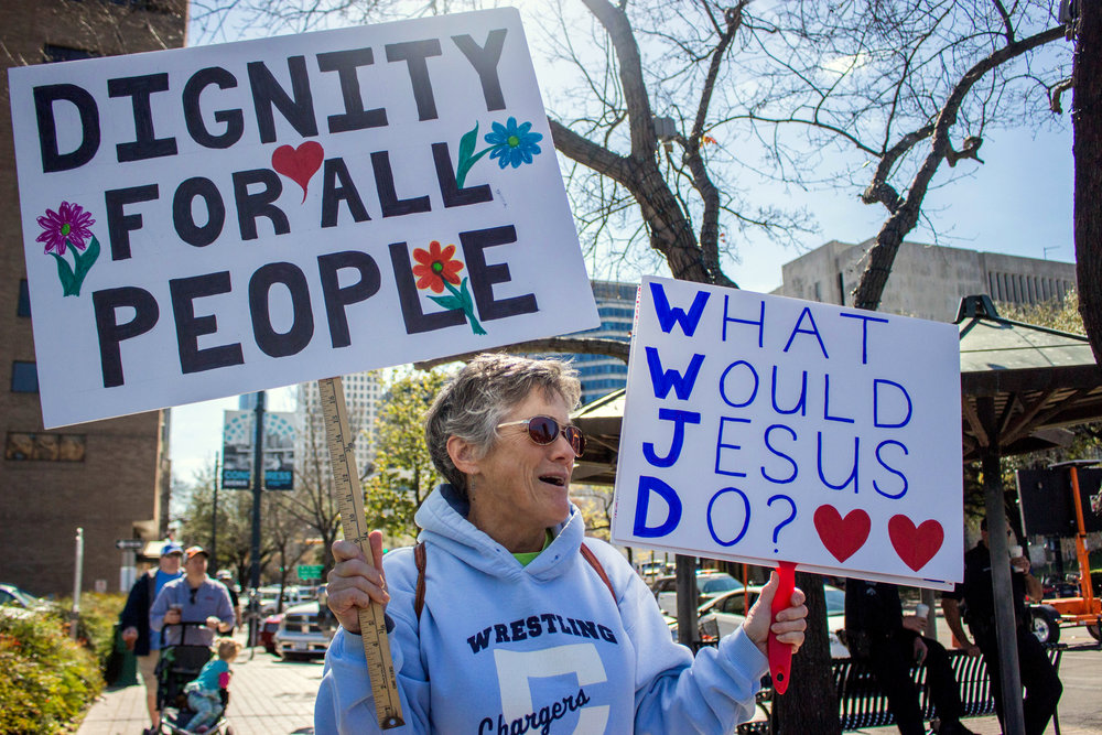 "Claire Kennedy holds two signs at the ""No Ban, No Wall"" protest. One reads, ""Dignity for all people"" and the other says, ""What Would Jesus Do?"""