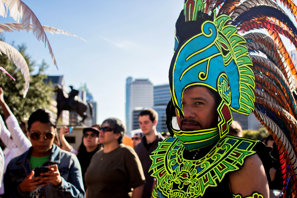 "Santos Diaz wears a green headdress at the ""No Ban, No Wall"" rally."