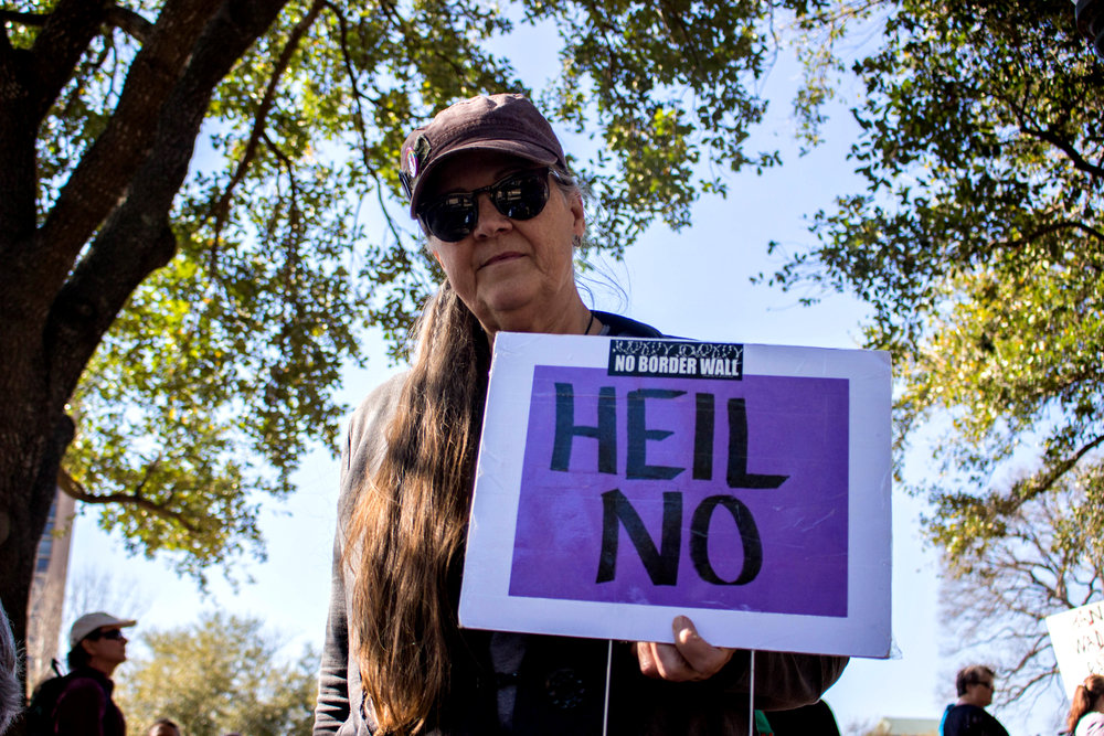 "A woman at the rally holds a sign that says, ""Heil no"" at the ""No ban, no wall"" rally on Saturday."