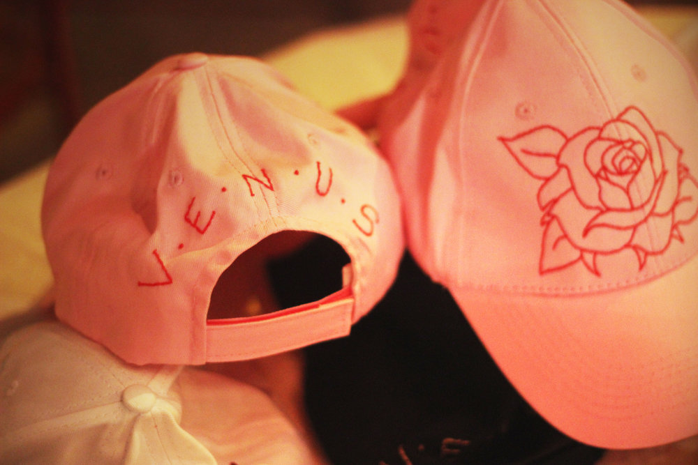 Hand-embroidered hats created for sale at the event.