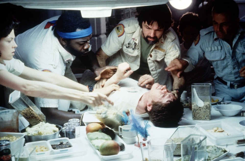 "A still from ""Alien"" (1979), just before the chest of a crew member bursts, creating the films' dire conflict. Photo courtesy of cinemablography.com."
