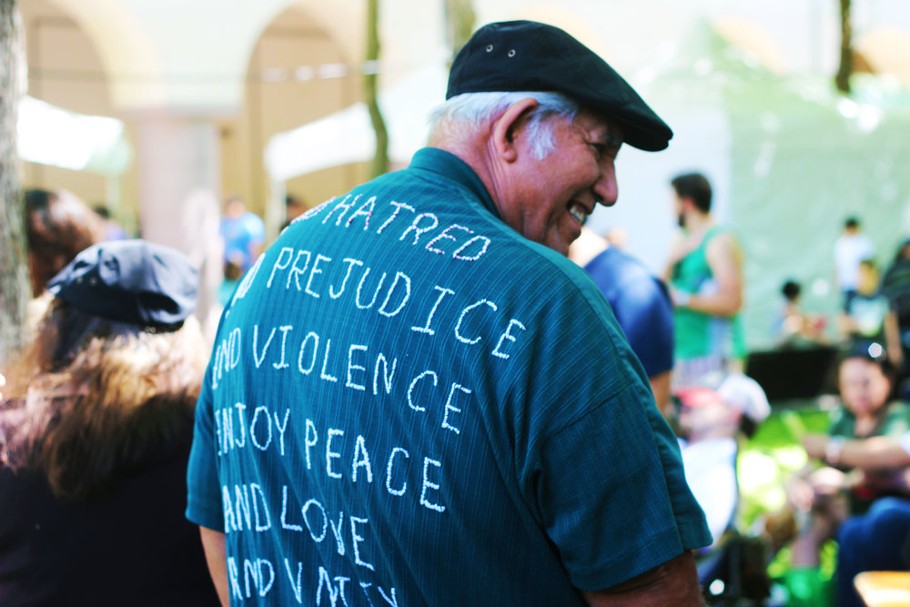 "After clapping along to a performance by the UT Austin Mariachi Ensemble, Enrique Cantu shows off the back of his shirt. Embroidered by his wife, the message reads, ""End Hatred and End Prejudice and End Violence. Enjoy Peace And Love and Unity."""