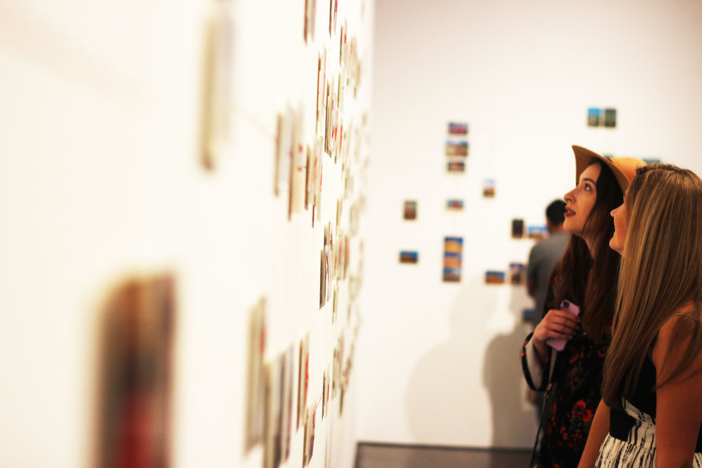 "People walk through walls of ""Paranormal Postcards"", a series a part of of the newly installed  ""Curiouser"" that interconnects a world view through postcards and red thread."