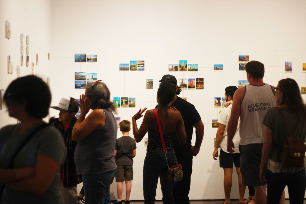 "People walk through walls of ""Paranormal Postcards,"" a series a part of of the newly installed  ""Curiouser"" exhibit that interconnects a world view through postcards and red thread."