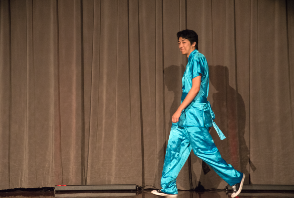 Eric Luo walks the stage in a shiny blue Chinese ensemble and modern American sneakers.