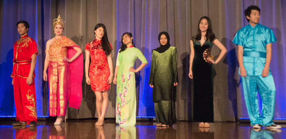 The students from different Asian student organizations pose together during the finale of the runway show.