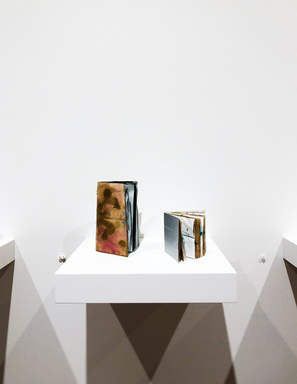 The colorful, recycled quality of these books is part of a stylistic theme that is present throughout the exhibit.