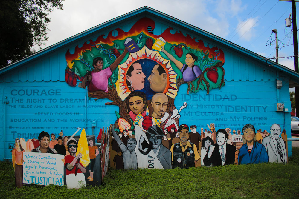 Mural of Chicanx activists decorate the side of Fuerza Unida's building.