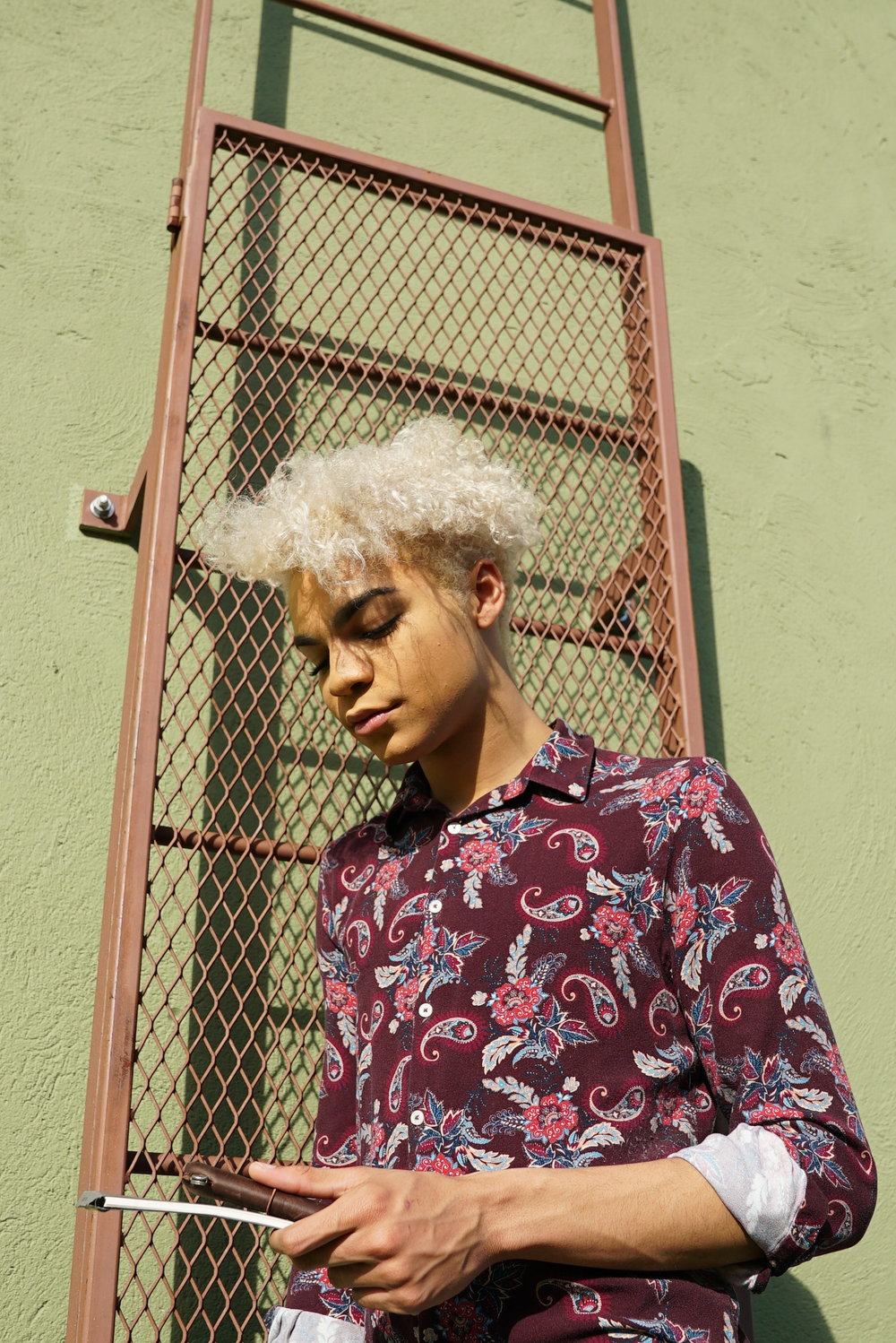 Lewis wears a bright paisley button-down suitable for class and work.