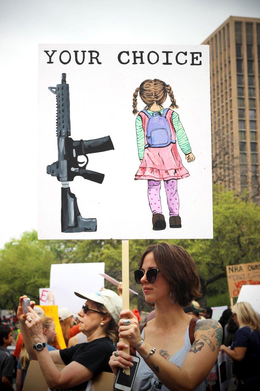 A woman raises her sign up high.
