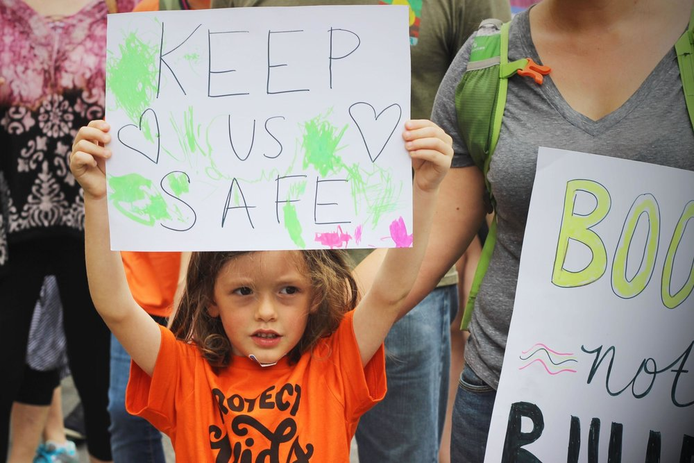 Standing alongside her mother, a young girl lifts up a sign.