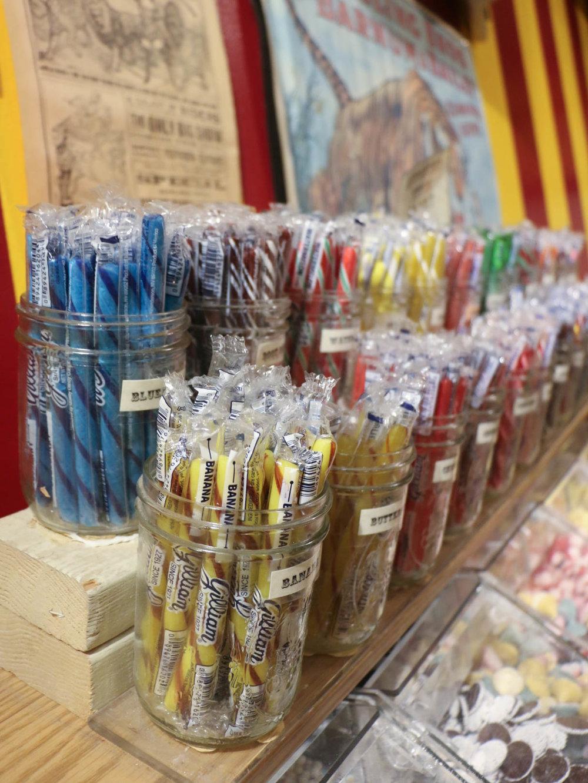 Assorted stick candies sit on top of Big Top's self-serve bins.