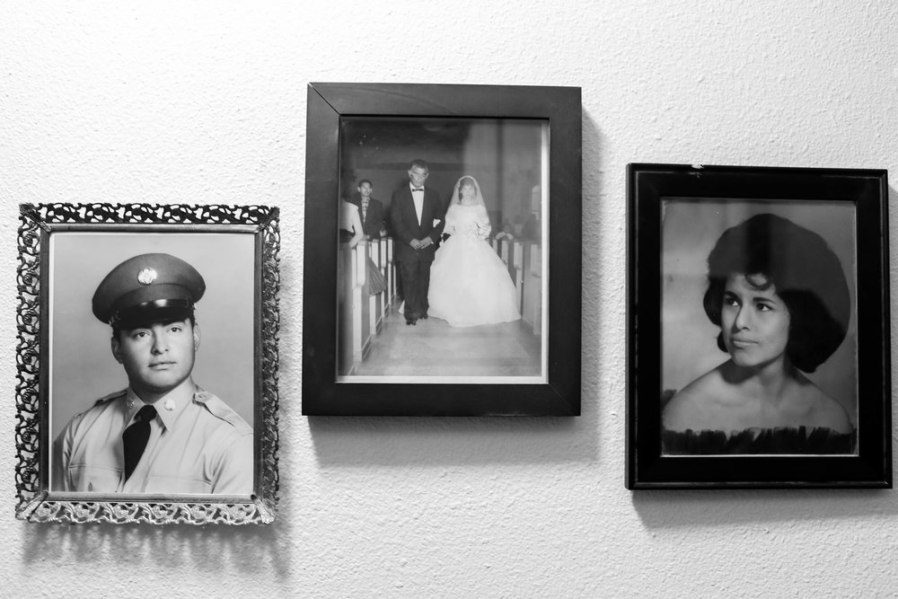 Near Don Antonia's altar displays hangs photos of first-generation aunts and uncles of the family.