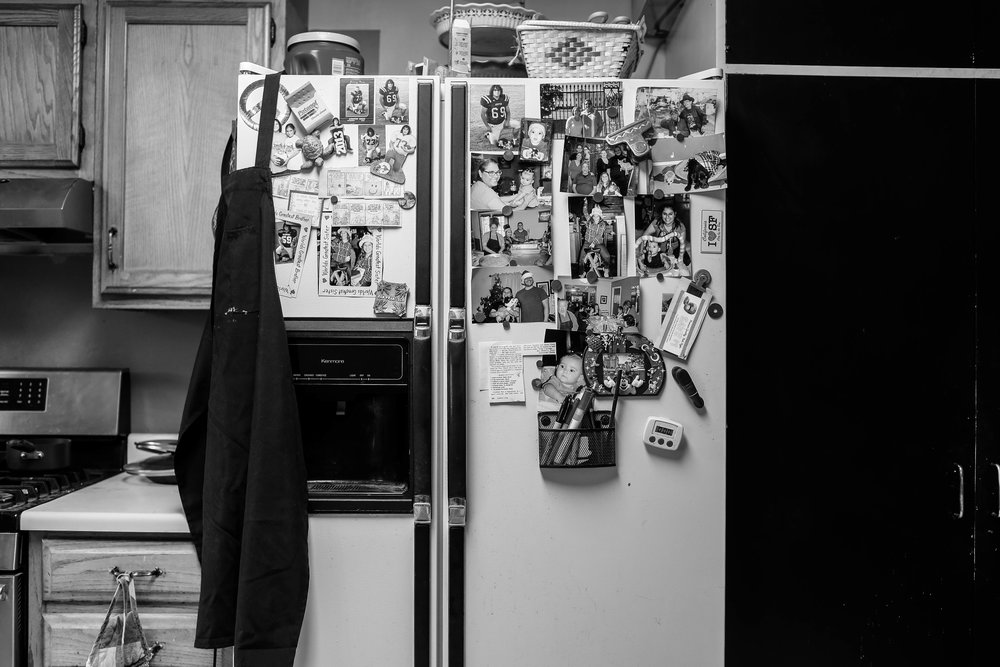 Pictures cover the refrigerator in the kitchen. The Cortez family refer to this as the wall of fame, their version of the walk of fame. Most members of the family can be found on here.