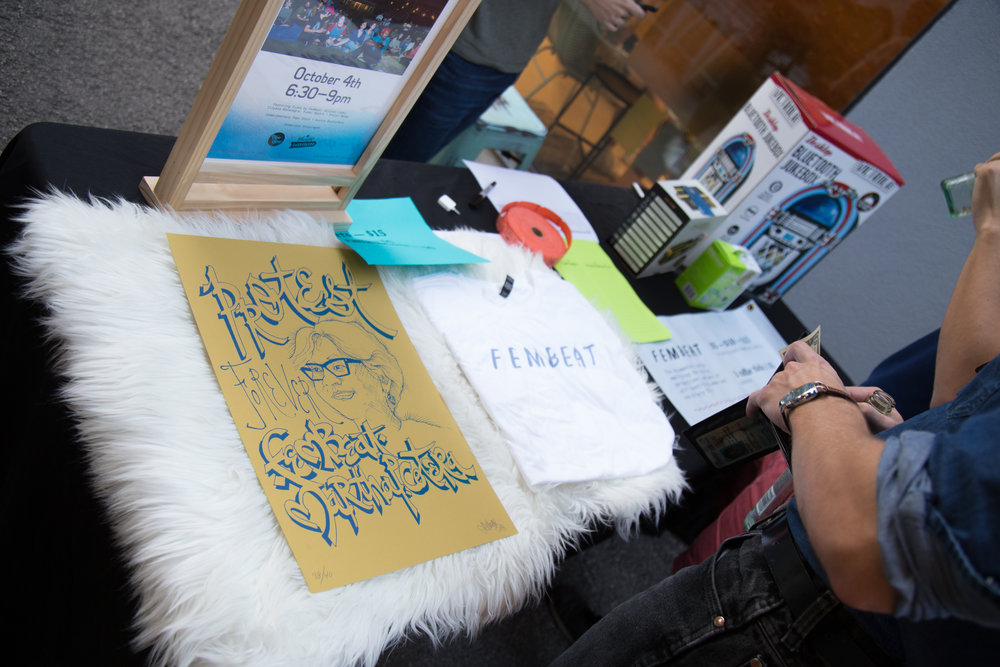 The front table at the FemBeat Film Festival displayed merchandise and raffle prizes.