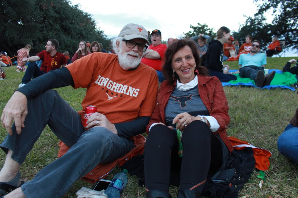 Silvia Huntsman and Tom Roudedusa casually sit on the grass facing the stage, waiting for the last performance of Longhorn City Limits to go on.