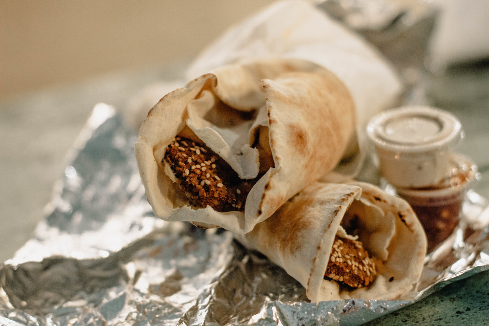 Two falafel wraps with a side of tahini and hot sauce.