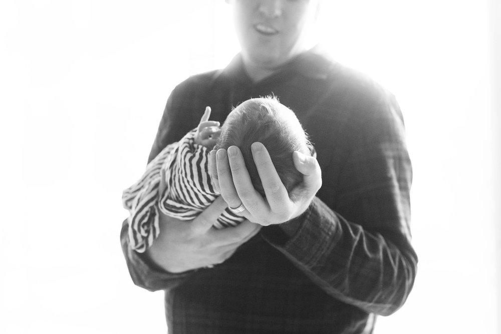 Dad holding newborn- Lifestyle Newborn Photogrpaphy